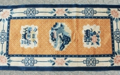 A CHINESE WOOL RUG with three motifs, orange ground