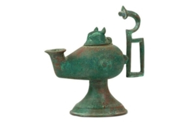 A FOOTED BRONZE OIL LAMP Iran, 10th - 12th century Of