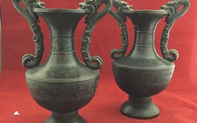 A pair of Chinese bronze vases, each with two dragon handles...