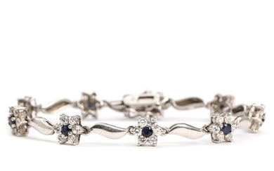 A sapphire bracelet set with nine round-cut sapphires and numerous clear gemstones, mounted in sterling silver. L. 19 cm.