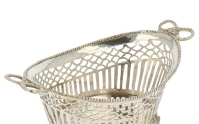 Bonbon basket with ajour openwork side and finished with molded bow handles and soldered pearl rim silver.