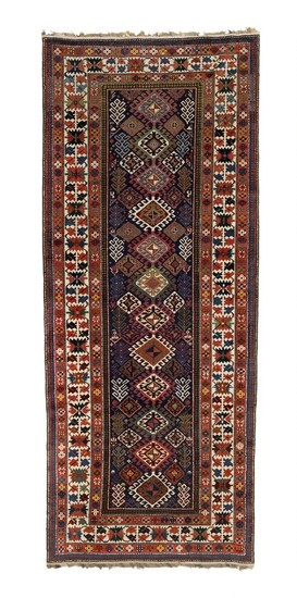 An antique Shirvan rug, Caucasus. Design of hooked linked diamonds on a blue field surrounded by a classical crab border. 19th century. 315×131 cm.