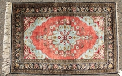 A FINE PERSIAN SILK RUG with central motif on a red