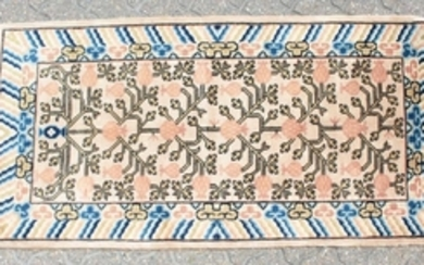 A CHINESE WOOL RUG with central motifs and blue and