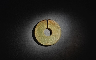 A SUPERB AND RARE ARCHAIC CELADON AND RUSSET JADE SLIT DISC (JUE) EASTERN ZHOU DYNASTY
