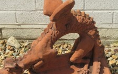 A terracotta roof ridge tile surmounted by a dragon on a V r...