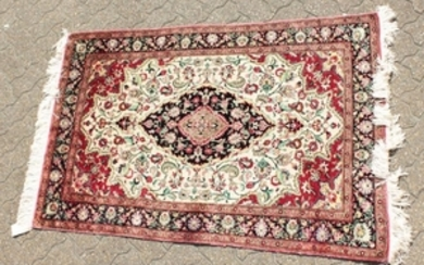 A FINE PERSIAN QUM SILK RUG with a central oval motif