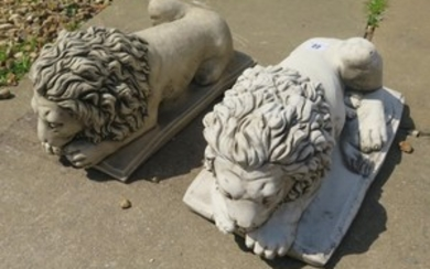 A pair of stone effect recumbent lions in the style of Canov...