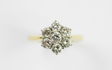 A diamond set cluster ring, designed as a central claw set b...