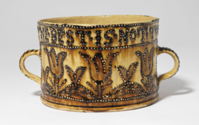 A STAFFORDSHIRE SLIPWARE TWO-HANDLED BRAGGET-POT, DATED 1699