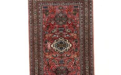 An Ardebil carpet, Persia. Geometrical medallion design with human figures and animal motifs. Field color at centre and main border with silk. 268×169 cm.
