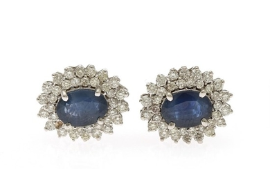 A pair of sapphire and diamond ear studs each set with an oval-cut sapphire encircled by numerous brilliant-cut diamonds, mounted in 14k white gold. (2)