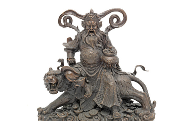 A late 19th / early 20th century Asian bronze model of a deity seated on a tiger, possibly showing the god of wealth Tsai Shen Yeh