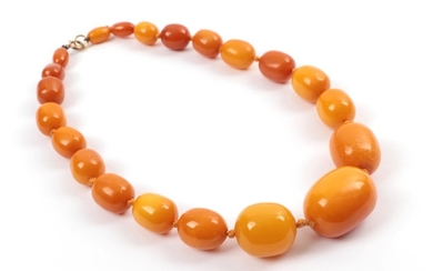 An Amber Bead Necklet, of 21 graduated barrel shaped beads,...