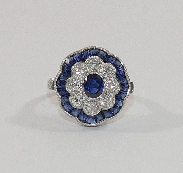 A sapphire and diamond oval flower head target cluster ring,...