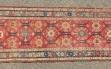 A CAUCASIAN RUNNER with typical motifs in red and blue.