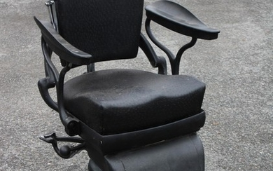 A vintage black leather and painted metal barbers chair, the...