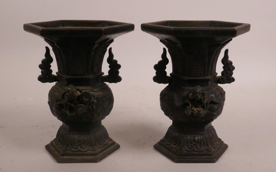 A pair of Oriental bronze two handled vases with raised deit...