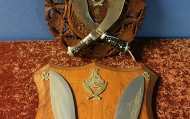 Carved wood wall plaque mounted with two Kukri type knives w...