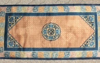 A CHINESE WOOL RUG with central motif and patterned