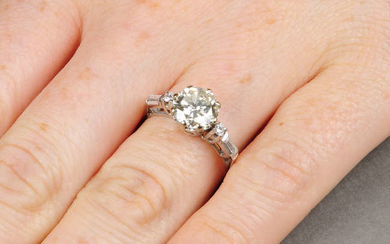 A diamond single-stone ring, with single and baguette-cut diamond shoulders.