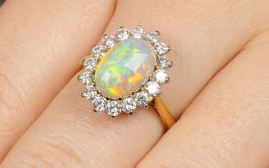 An 18ct gold oval opal cabochon and brilliant-cut diamond cluster ring.