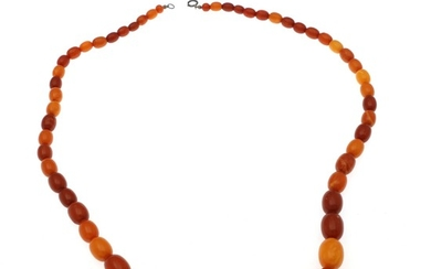 A graduated amber necklace set with numerous oval polished amber beads and a clasp of silver. Pearl measurements app. 9×7–24 17.5 mm. L. 74 cm.