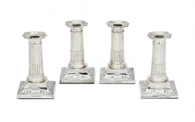 A set of four Edwardian silver short columnar candlesticks by The Goldsmiths & Silversmiths Co. Ltd