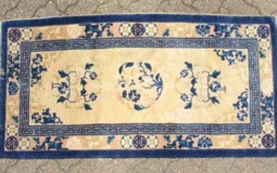 A CHINESE WOOL RUG with three central motifs in blue