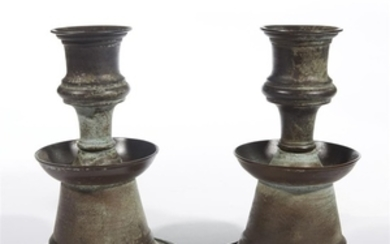 A pair of Islamic style metal candlesticks