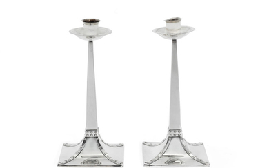 A pair of Edwardian Arts and Crafts silver candlesticks