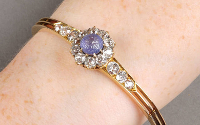 An early 20th century gold, foliate carved sapphire and old-cut diamond cluster hinged bangle.