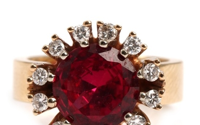 A ruby and diamond ring set with a round-cut ruby encircled by brilliant-cut diamonds, mounted in 14k gold. Size app. 52.