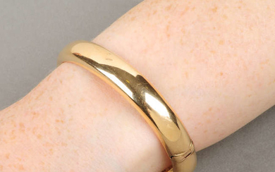 An early 20th century 15ct gold hollow, hinged bangle.