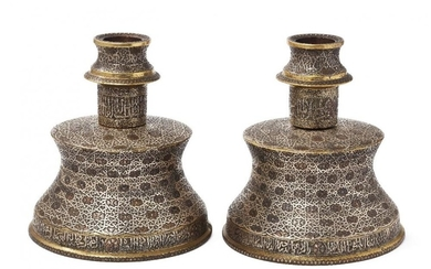 Two large silver- and copper-inlaid brass candlesticks...
