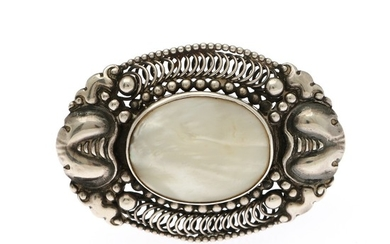 A mother of pearl brooch set with an oval piece of mother of pearl, mounted in sterling silver. 4.2×6 cm.