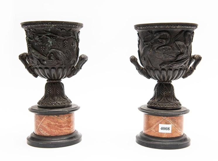 A PAIR OF FRENCH BRONZE URNS WITH DEEP CAST DECORATION ON MARBLE BASES (A/F CHIPS TO MARBLE)