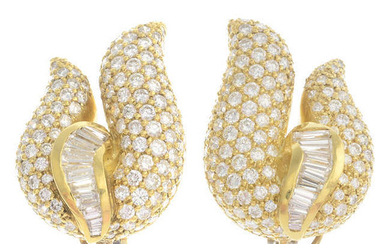 A pair of pave-set and tapered baguette-cut diamond scroll earrings.