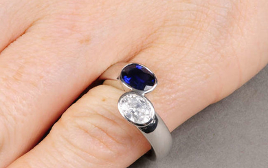 A platinum oval-shape diamond and sapphire two-stone crossover ring.