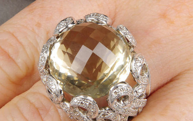 A multifaceted citrine dress ring, with diamond crossover loop surround.