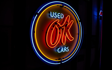 An OK Used Cars neon sign