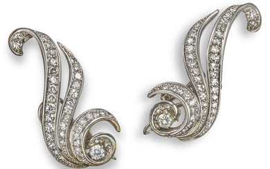 A pair of diamond scroll earrings, set with gradua…