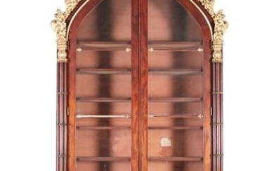 A REGENCY ROSEWOOD AND PARCEL GILT BOOKCASE, in th…